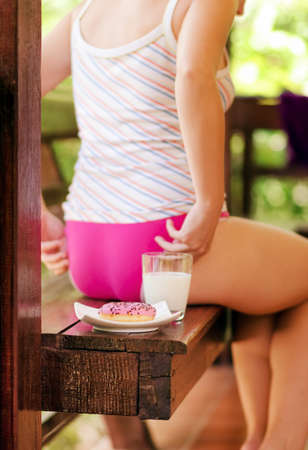 teen girl underwear: Young woman sitting on terrace with milk and donut.