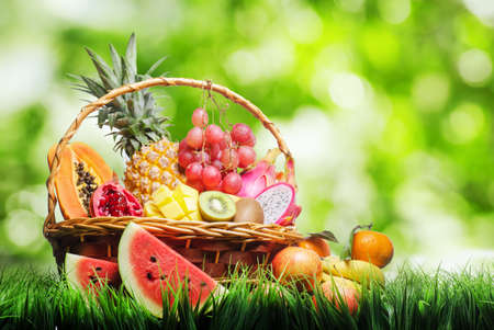 apples basket: Basket of tropical fruits on green grass