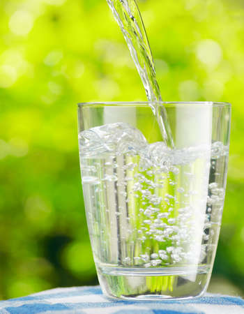 purified: Glass of water on nature background.