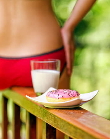 Young woman sitting on terrace with milk and donut. photo