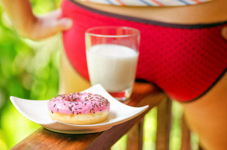 sexy food: Young woman sitting on terrace with milk and donut.