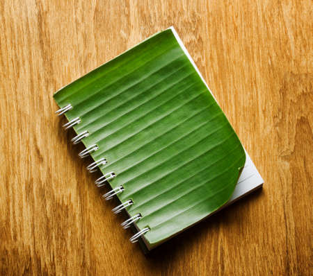 Notepad with cover of leaf lies on wooden board. photo