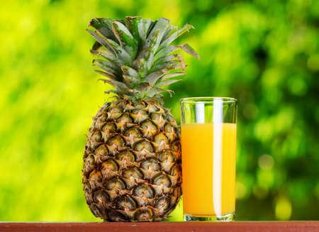 Glass of pineapple juice in a garden