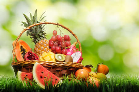 Basket of tropical fruits on green grass. photo