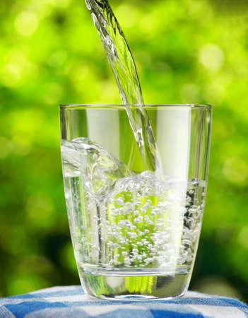 Vaso de agua sobre fondo de naturaleza.