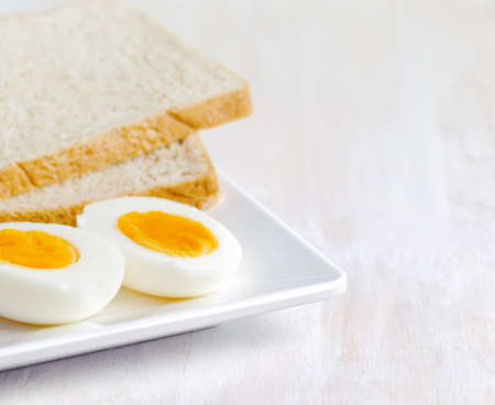 Boiled egg and toasts on white plate. Stock Photo