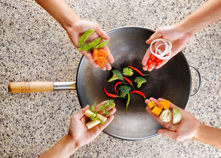 oriental cuisine: Four hands puts fresh vegetables in the wok. Cooking concept. Stock Photo