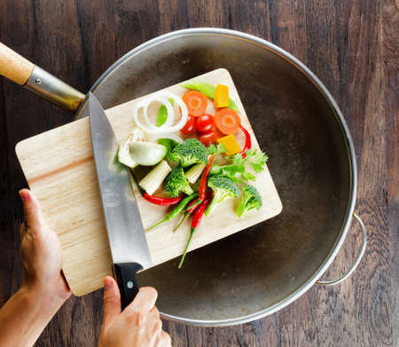 Fresh vegetables on the cutting board are falling in the wok. Concept of cooking.