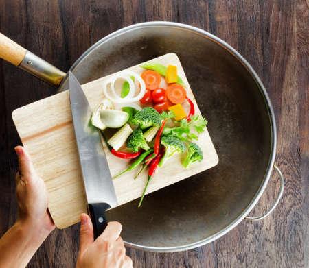 cuchillo: Verduras frescas en la tarjeta de corte están cayendo en el wok. Concepto de cocinar. Foto de archivo
