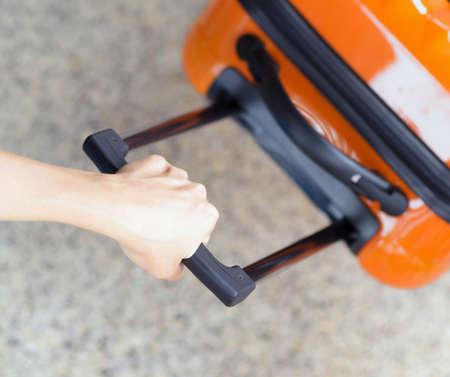 mujer con maleta: Mujer sostiene maleta de color naranja en la mano. Foto de archivo