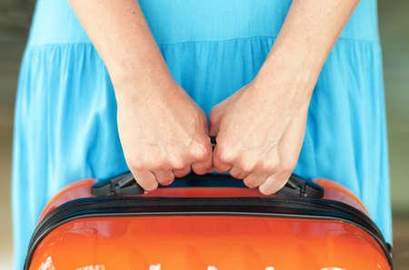mujer con maleta: Mujer en vestido azul tiene maleta de color naranja en las manos.