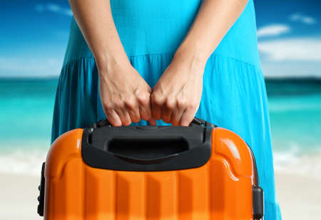 Woman in blue dress holds orange suitcase in hands on the beach background. Stock Photo