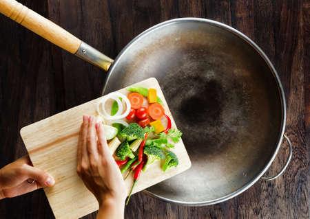 Verduras frescas en la tarjeta de corte están cayendo en el concepto de la cocina wok Foto de archivo