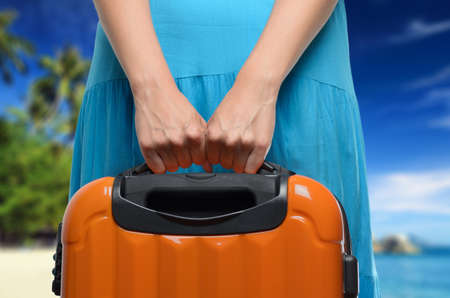 packing suitcase: Woman in blue dress holds orange suitcase in hands on tropical landscape background  Stock Photo