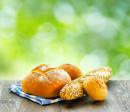 Fresh bread and checkered napkin on  wooden table on rural background. photo