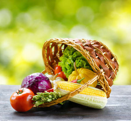 Fresh vegetables in the basket on wooden table. photo