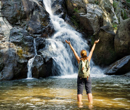 adventure sports: Female hiker looking at waterfall.