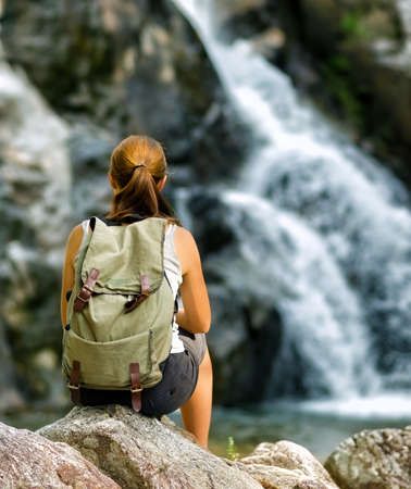 woman hiking: Female hiker looking at waterfall.