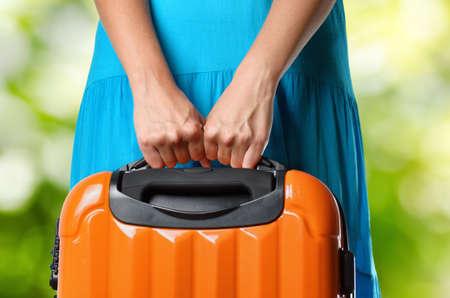 Femme en robe bleue détient valise orange dans les mains sur fond naturel.