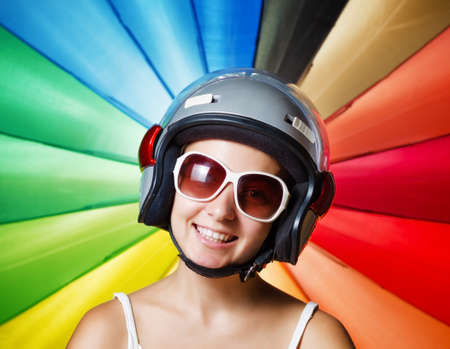 Funny girl in helmet having fun. Multicolored background. Stock Photo - 18765783