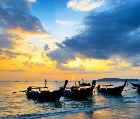 Traditional thai boats at sunset beach. Ao Nang, Krabi province. photo