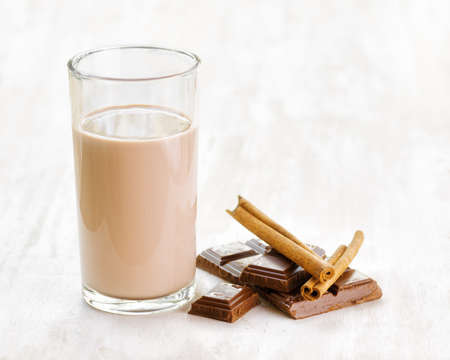 children breakfast: Chocolate milk with chocolate and cinnamon on white wooden table.