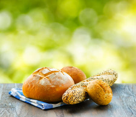 Fresh bread and checkered napkin on  wooden table on rural background.