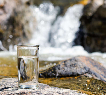 Glass of water by waterfall.