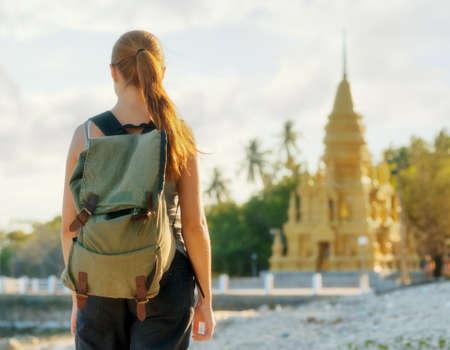 Young woman looking at golden pagoda. Hiking at Asia.