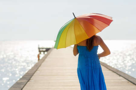Young woman walking on the pier with umbrella. photo