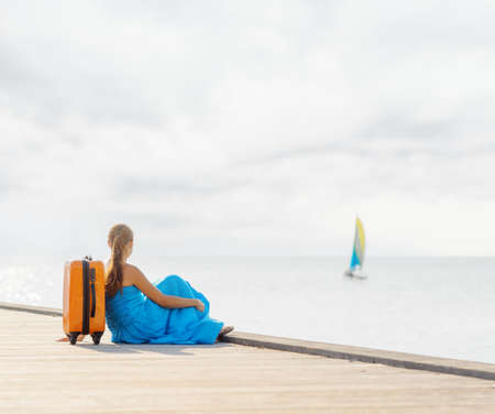 Young woman sitting on wooden pier. Zdjęcie Seryjne