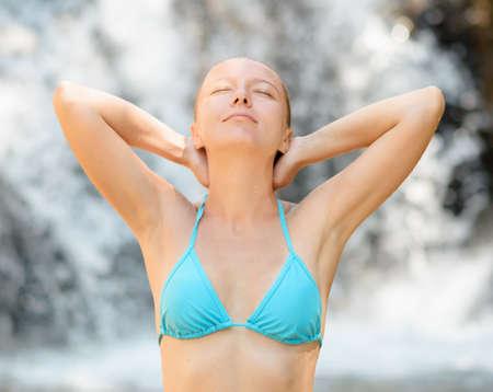 wet bikini: Young woman relaxing in waterfall. Stock Photo