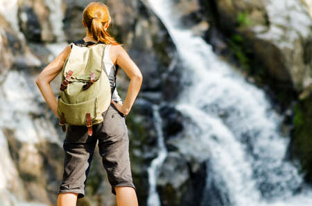 Female hiker looking at waterfall. photo