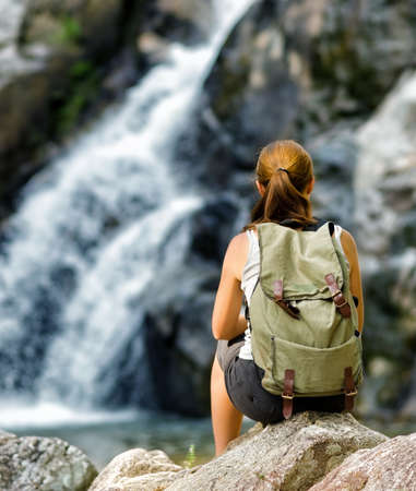 Female hiker looking at waterfall  photo