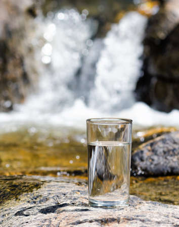 Glass of water by waterfall  photo