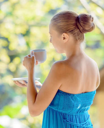 woman drinking tea: Young woman drinking coffee on morning terrace.