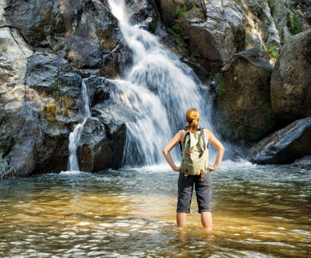 Female hiker looking at waterfall  Stock Photo