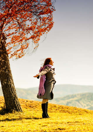 Young woman standing on an autumn hill. Stock Photo