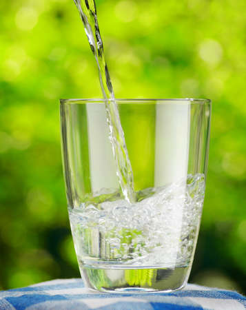 Glass of water on nature background. Stock Photo - 20384840