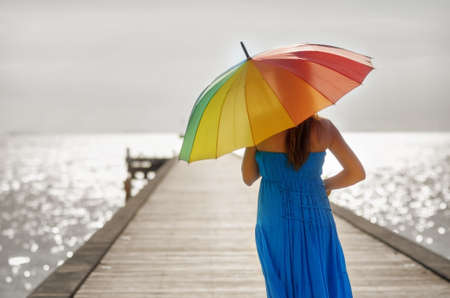 Young woman walking on the pier with umbrella.