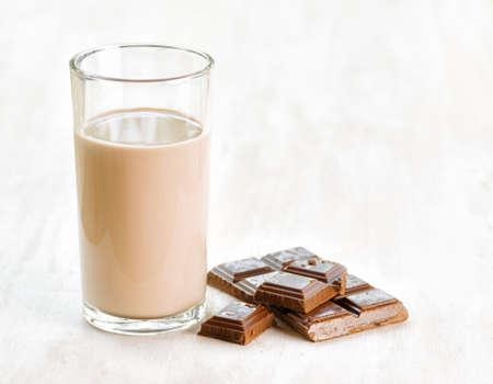Chocolademelk en chocolade op witte houten tafel. Stockfoto