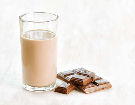 chocolate with milk: Chocolate milk and chocolate on white wooden table. Stock Photo
