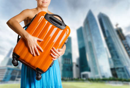 Woman in blue dress holds orange suitcase in hands  photo