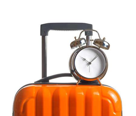 Alarm clock on orange suitcase.