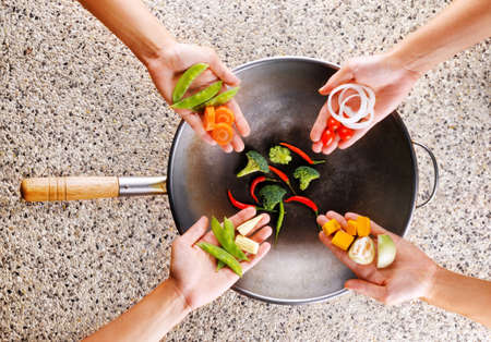 four hands: Four hands puts fresh vegetables in the wok. Cooking concept. Stock Photo