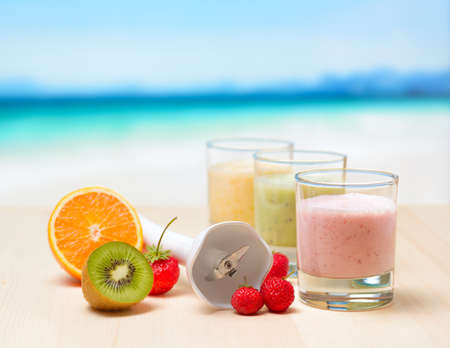 Fruit smoothie on wooden table on tropical beach. photo