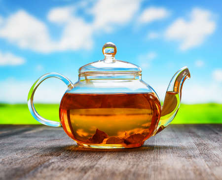 Teapot of fresh tea on natural background. photo