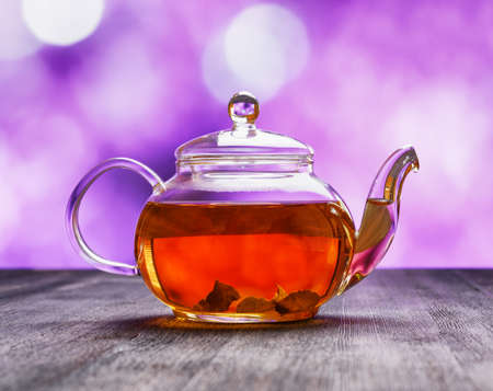 Teapot of fresh tea on purple background. photo