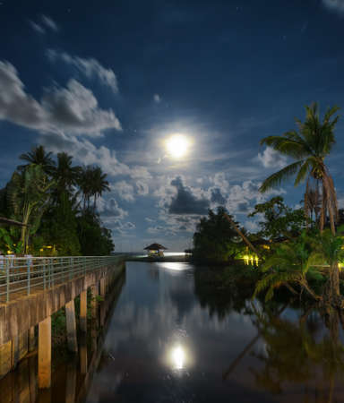 Gazebo and moon in waters reflection. Night landscape. photo