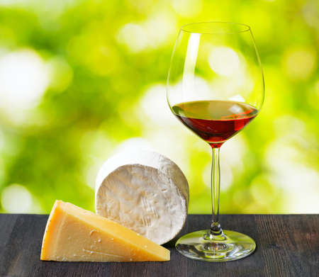 Cheese and glass of wine on nature . photo